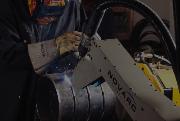 A welder working with a Novarc robotic welding machine
